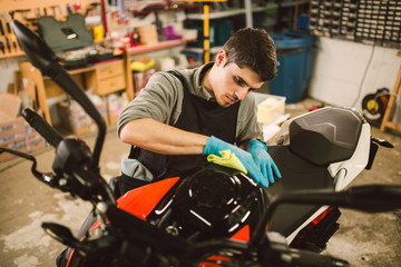 Mechanic polishing and cleaning a motorcycle