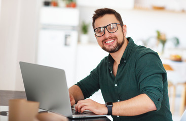Happy man businessman, freelancer, student working at computer at home .