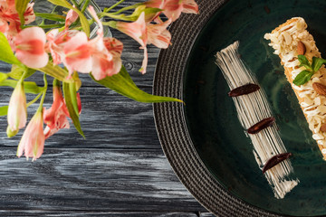 top view of delicious dessert with almonds on plate and flowers on wooden table
