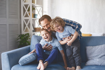 Portrait of laughing dad hugging beaming kids having entertainment on sofa in living room....