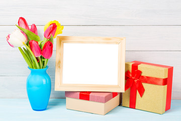 Colorful red spring tulip flowers in nice blue vase and blank photo frame with giftboxes on light wooden background as greeting card. Mothersday or spring concept