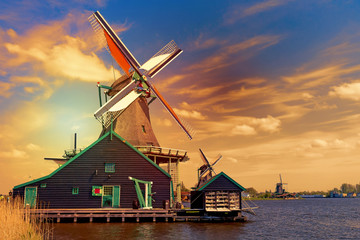 Dutch typical landscape. Traditional old dutch windmills against blue cloudy sky in the Zaanse Schans village, Netherlands during sunset. Famous tourism place.