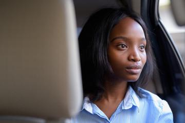 Young beautiful African Zulu businesswoman riding inside the car
