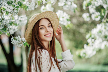 Young beautiful happy smiling girl with healthy  white teeth, radiant skin, long natural hairwalking in flowering cherry garden. Beauty, health care concept. Copy, empty space for text