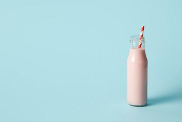 strawberry milkshake in bottle with drinking straw on blue background