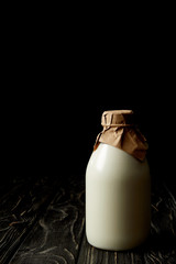 closeup view of fresh milk in bottle wrapped by paper on black background