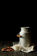 closeup view of milk in glass and aluminium can, chocolate cookies and sackcloth on black background