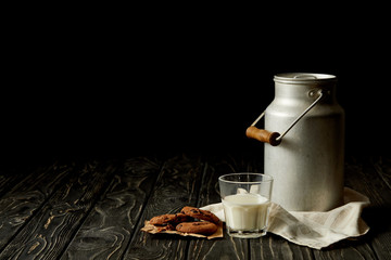 milk in glass and aluminium can, chocolate cookies and sackcloth on black background