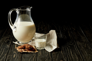 closeup view of fresh milk in jug and glass, chocolate cookies and sackcloth on black background