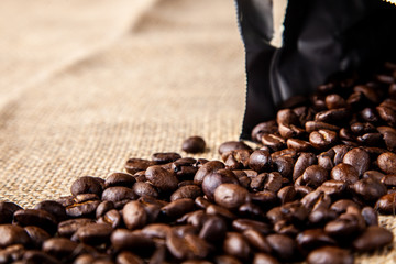 Open bag of coffee beans spilled onto a jute cloth