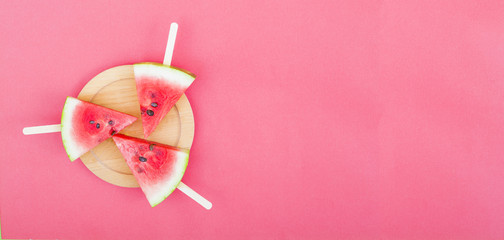 watermelon slice with stick on red background