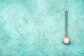 Vintage bronze pocket watches with five minutes to twelve o'clock hanging on nail front old mint green concrete wall textured background. Retro style filtered photo