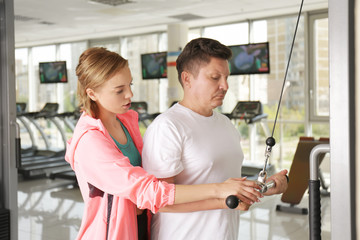 Mature man with young trainer in gym