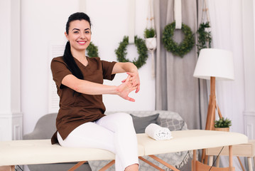 Smiling female doctor looking at camera and sitting on massage table in modern medical office. Professional female masseuse in light room.