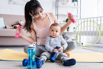 young fit mother doing exercises while sitting on yoga mat with her little child at home