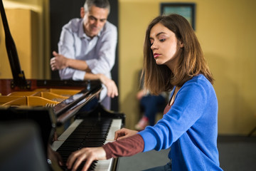 Two young women at a piano time with a teacher