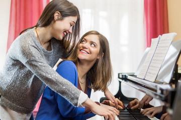 Teenage girls playing piano together