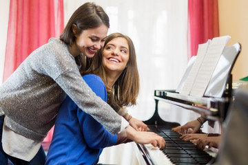 Two female playing the piano.