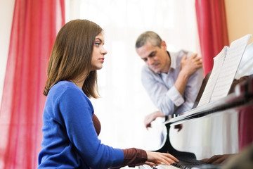 The piano teacher gives classes to a young woman