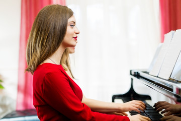 Two young women play on the piano