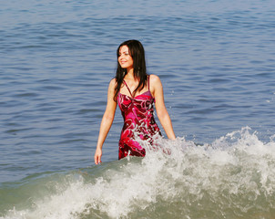 Young smiling woman standing in sea waves