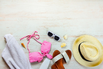 Top view of two pieces pink swimming suit and beach accessoties over wooden background. Copy space=