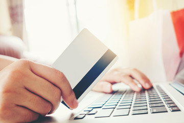 Close up credit card,woman shopping online using laptop enjoying in home