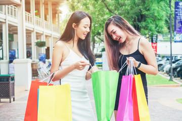 Happy Asian women friendship Enjoying Spending shopping bags in Fashion shopping street