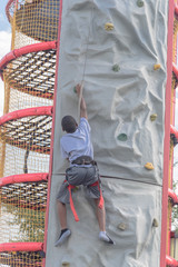 Rearview of unidentified little boy climbing an inflatable rock wall at public event park.
