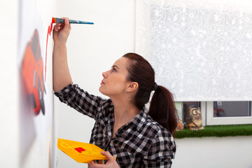 Young dark-haired female mom in plaid shirt draws on a white wall wall a drawing in a boy's room