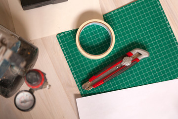 A close-up of a set of tools: a paper cutting knife, a millimeter paper, an adhesive tape, an airgrove. View from above