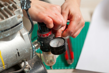 Close-up of a woman working adjusts the sensor on a metallic gray airbrush