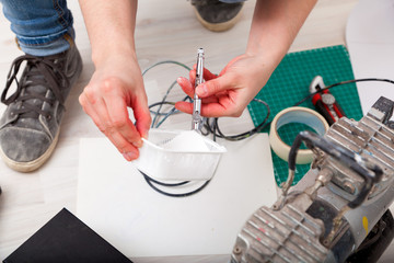 A close-up of a woman artist in jeans and sneakers prepares an airbrush to work in front of painting walls, on the floor there is a millimeter paper, an adhesive tape and a knife for cutting paper.