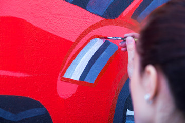 Close-up of a female artist in black and white shirt draws a red car on a wall with a pencil on a white wall in a children's room