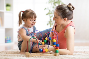 Child toddler girl and mom playing with educational toy in nursery at home.
