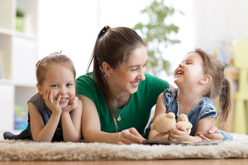 kids and their mother reading a book on floor in cozy living room