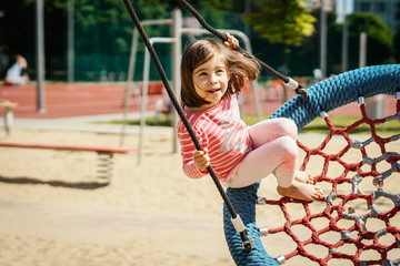 beautiful little girl is swinging on a swing at the playground on a summer day