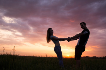 Silhouette of a young couple on sunset sky