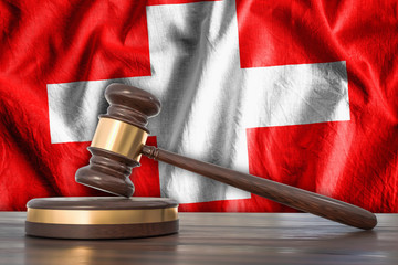 Wooden gavel and flag of Switzerland on background - law concept