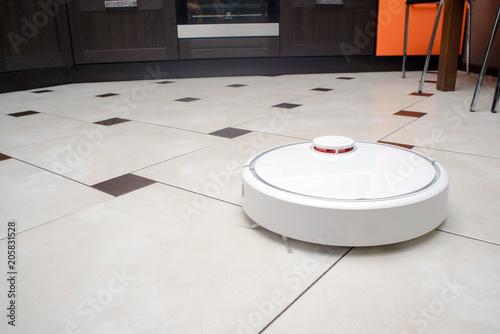 Robotic Vacuum Cleaner On Ceramic Tile Floor In Kitchen.