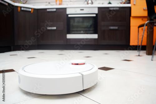 Robotic vacuum cleaner on ceramic tile floor in kitchen.\