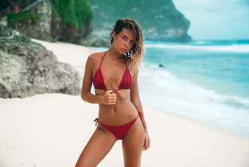 A brunette with curly hair strolls by the sea. Slender model in a red bikini posing on the beach.