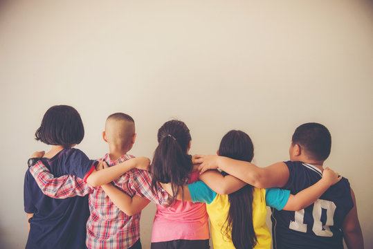 Group of kids friends arm around sitting together