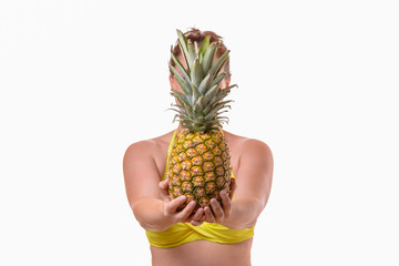 Woman in swimsuit holding pineapple