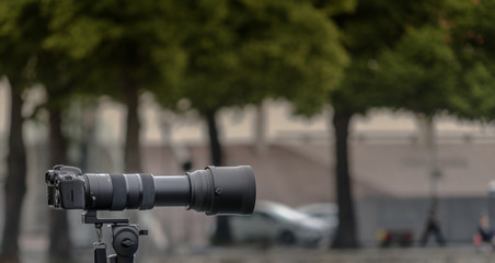 Tripod-mounted 35 mm camera with a large lens of long focal length against a deliberately blurred background