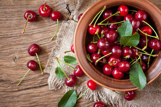 Fresh cherry in bowl on wooden background. vegetarian food. Summer time.