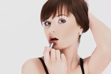 closeup. a young woman uses lip gloss