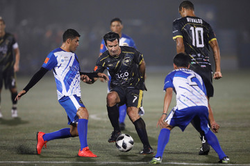 Former Portuguese soccer player Luis Figo plays ball with former Salvadorean soccer players Jaime Medina and Roberto Garcia during an exhibition match at Las Delicias Stadium in Santa Tecla
