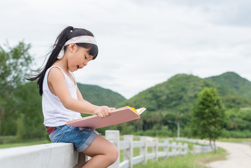 Beautiful smiling teenage girl in White blouse Sitting on a leak and read book, against green of summer park.