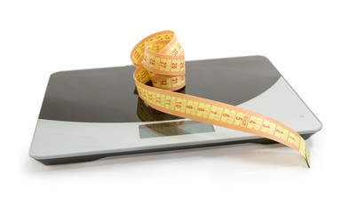 Tape-line on kitchen scales, concept of excess weight